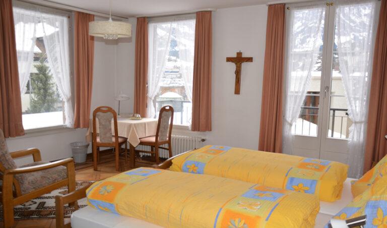 Doppelbett mit Tisch und Fenstern