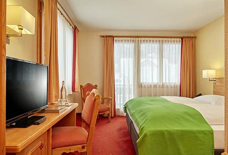 Zimmeransicht mit Bett, TV und Stühlen
