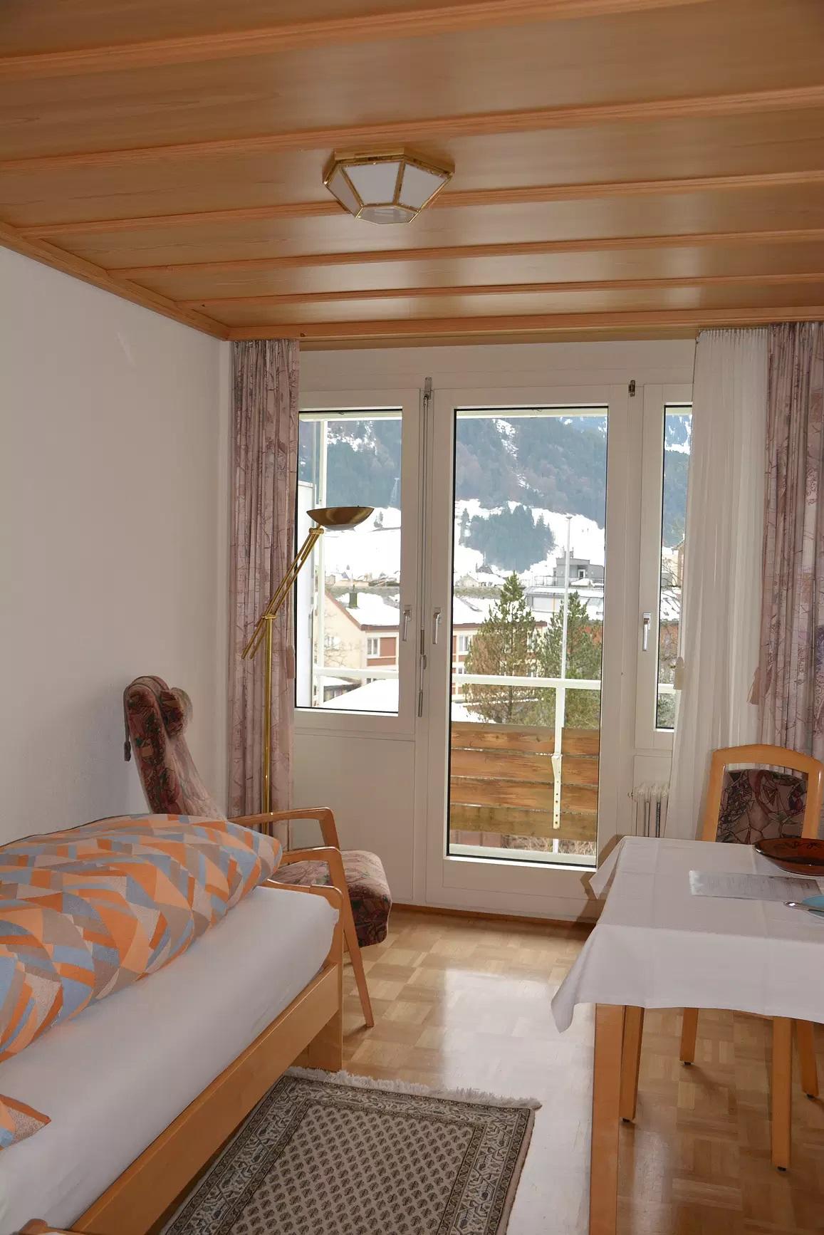 Zimmer mit Bett, Tisch und Aussicht aus dem Fenster
